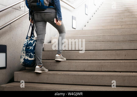 Woman with bag and backpack walking up stairs at the station - Stock Photo