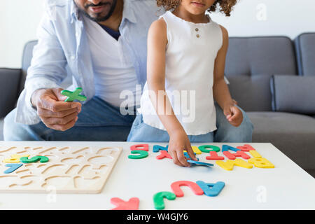Father and daughter playing with alphabet learning game at home - Stock Photo