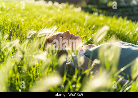 Young redheaded woman lying on meadow in a park - Stock Photo