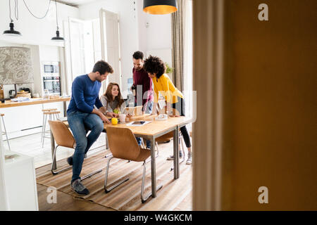 Four friends in dining room at home with book