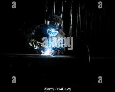 Industrial worker in protective clothing welding metal with welding torch - Stock Photo