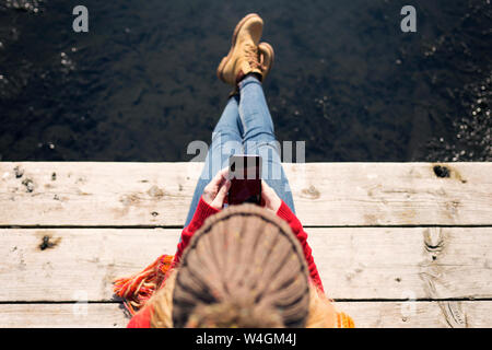 Young blond woman using smartphone at a lake in winter - Stock Photo