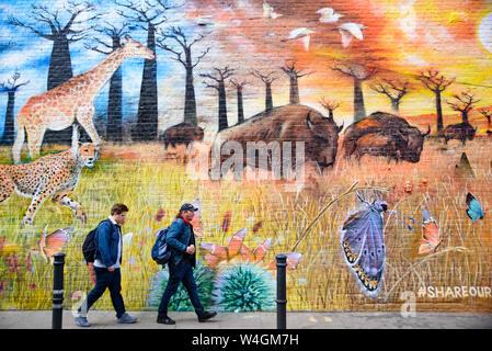 People passing by the graffiti wall art at Brick Lane Market in London, United Kingdom