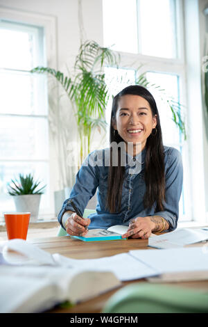 Portrait of happy woman working at table in office