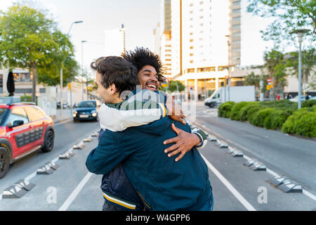 Two happy friends embracing in the city, Barcelona, Spain