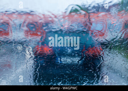 View through windscreen on rainy evening while waiting at level crossing - Stock Photo