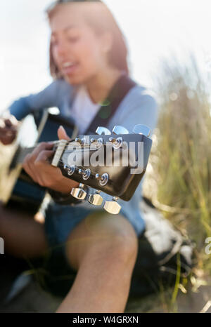 Close-up of young woman singing and playing guitar on the beach