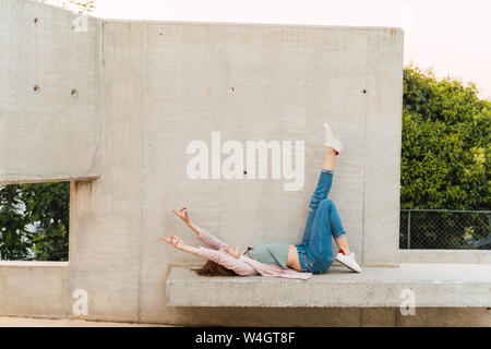 Young redheaded woman with raised arms lying on concrete bench - Stock Photo