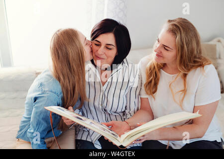 Grown up daughters visiting their mother, looking at photo album - Stock Photo
