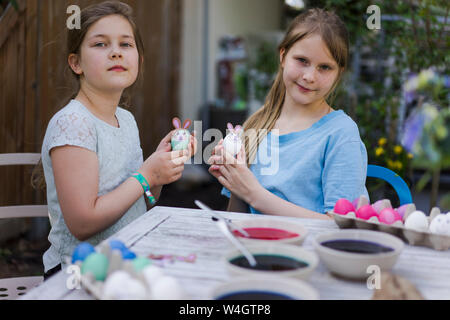 Portrait of two girls decorating Easter eggs on garden table - Stock Photo