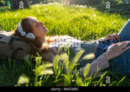 Young redheaded woman with headphones and smartphone in a park - Stock Photo