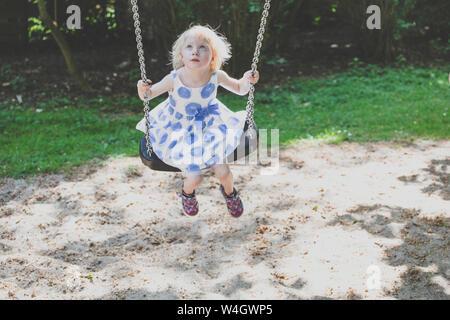 Portrait of blond little girl wearing summer dress sitting on a swing looking up