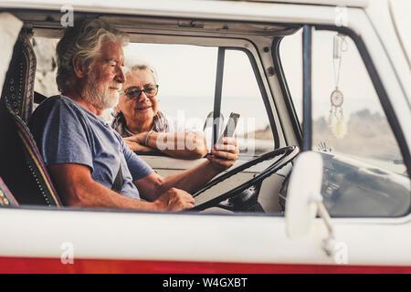 Senior couple traveling in a vintage van, using smartphone - Stock Photo