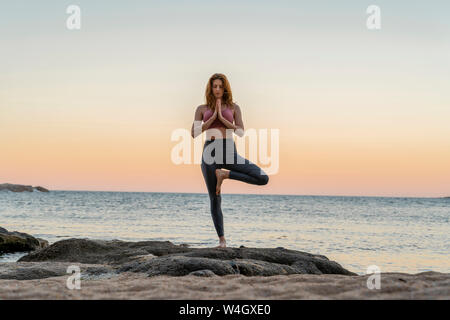 Young woman practicing yoga on the beach, doing tree pose, during sunset in calm beach, Costa Brava, Spain Stock Photo
