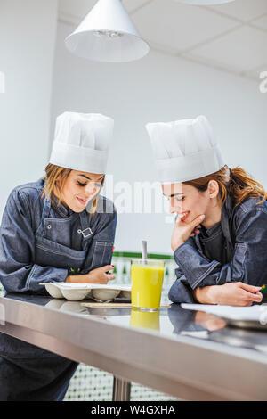 Junior chefs prepairing a dessert - Stock Photo