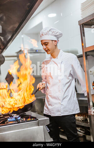 Junior chef with pan of flames in traditional spanish restaurant kitchen - Stock Photo