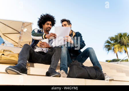 Two casual businessmen sitting on stairs working on paper - Stock Photo