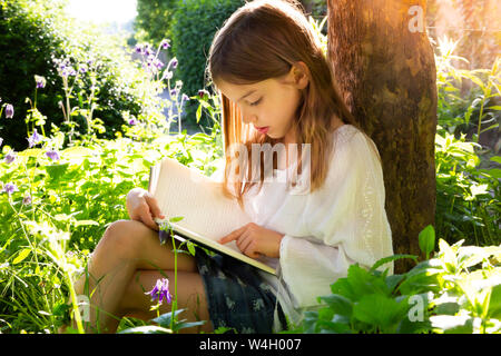 Little girl leaning against tree trunk reading a book
