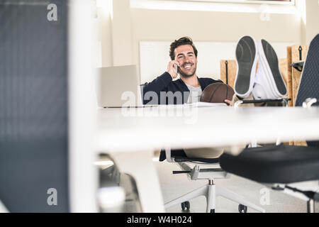 Young businessman sitting in office, with feet on desk, talking on the phone - Stock Photo