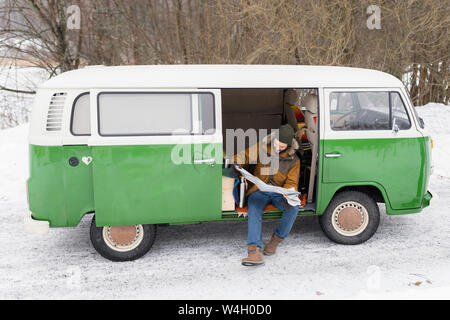 Man with electric van in winter landscape studying road map, Kuopio, Finland - Stock Photo