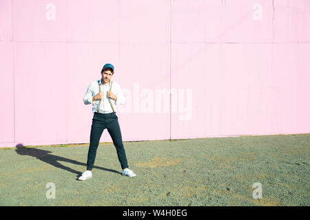 Young man in front of pink construction barrier, holding onto his suspenders - Stock Photo