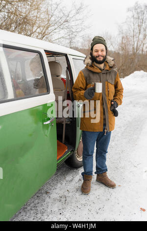 Portrait of smiling man with electric van in winter landscape, Kuopio, Finland - Stock Photo