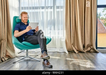 Young man sitting in armchair, listening music, using digital tablet Stock Photo