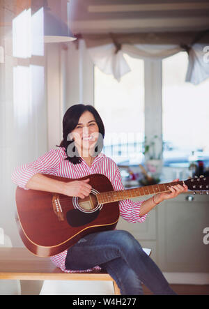 Portrait of smiling mature woman playing guitar at home