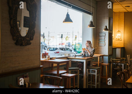 Young businesswoman using tablet in a bar - Stock Photo