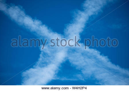 X Marks the Spot. X. The Letter X. An X in the sky. Two Airplane Contrails or Chemtrails in the Sky. Condensation Trail. Aircraft Contrail in Blue Sky - Stock Photo