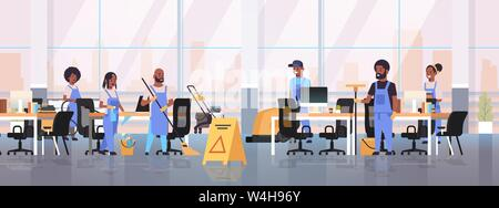 cleaners team in uniform working together cleaning service concept african american janitors using professional equipment modern co-working open space - Stock Photo