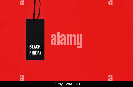 Black sale tag with Black Friday inscription on red background. - Stock Photo