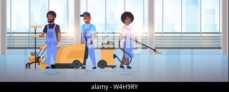 cleaners team in uniform working together cleaning service concept african american janitors using professional equipment modern hall interior - Stock Photo