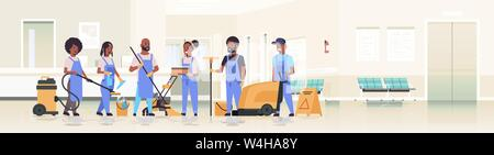cleaners team in uniform working together cleaning service concept african american janitors using professional equipment clinic reception hospital - Stock Photo