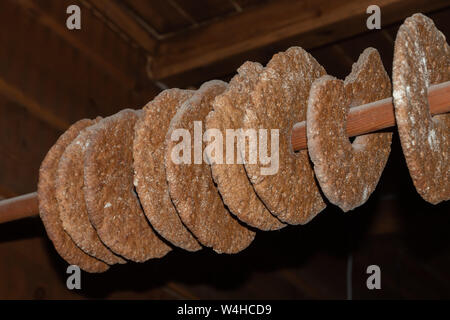 Rye bread drying on a pole. Traditional way to store bread in an farmhouse, hanging from a pole in the ceiling - Stock Photo