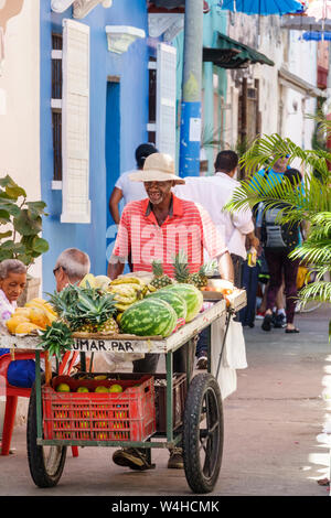 Cartagena Colombia Old Walled City Center centre Getsemani Hispanic Black man street fruit vendor pushing cart melons pineapples working - Stock Photo