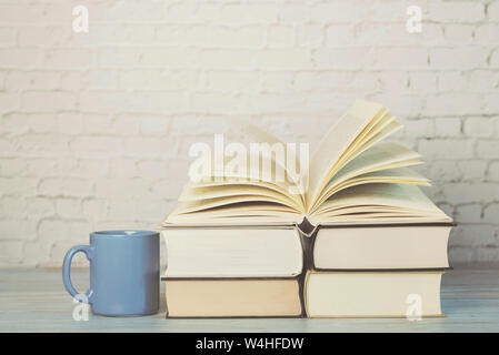 Stack of books with cup of coffee on wooden table - Stock Photo