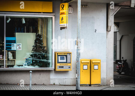 Freiburg im Breisgau, Germany - December 31, 2017: View of a post office in a shopping street downtown on a winter day - Stock Photo