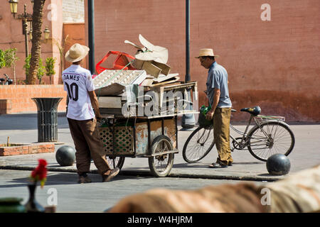 Street scene of local moroccan rubbish collector and cyclists around Markakech souk and city streets