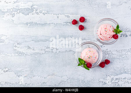 Raspberry ice cream balls with berries and mint leaves in glass bowls - Stock Photo