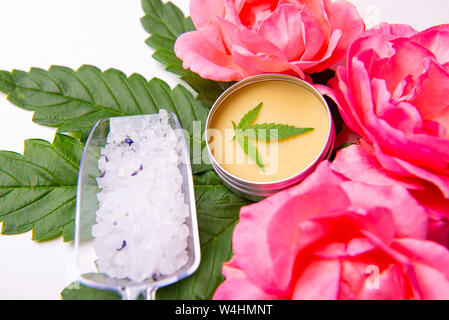 Cannabis infused beauty products with roses, merijuana leaves and CBD salve over white background - Stock Photo