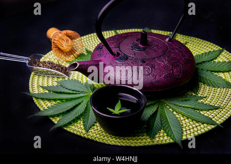 Cannabis infused tea concept with kettle and marijuana leaves isolated on black background - Stock Photo
