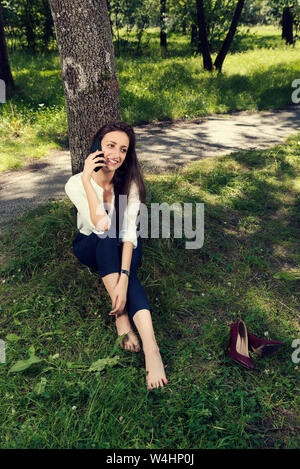 Business woman resting sitting under the tree without shoes and talking on the phone in a public city park Selective focus - Stock Photo