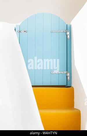 Small blue greek door and yellow steps on Santorini island, Greece - Stock Photo