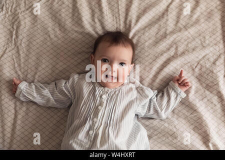 Cute newborn girl lying on the bed. The baby wants to sleep in the parent's bed. Stock Photo