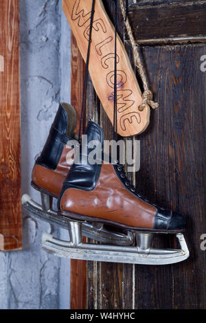 New Year concept of vintage hockey skates hanging on a wooden wall next to a sign saying Welcome, selective focus - Stock Photo