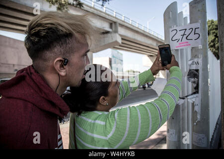 Tijuana, Mexico. 23rd July, 2019. Migrants from Honduras shoot a picture of the number of appointments given for asylum applications in the USA at the border point El Chaparral. Credit: Omar Martinez/dpa/Alamy Live News - Stock Photo