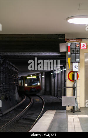 Nordbahnhof, Berlin, Germany - july 07, 2019: view from the platform into the illuminated railway tunnel with a train approaching in the distance - Stock Photo