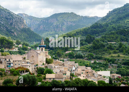 Beautiful view on Esglesia de Sant Bartolomeu in the old town of Valldemossa, Mallorca, Spain - sunlight and clouds create interesting lighting - Stock Photo