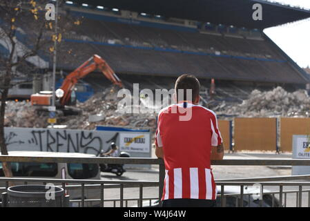An Atletico de Madrid fan looks at Vicente Calderón stadium during its demolition in Madrid.Vicente Calderon stadium was named after the club's former president and it was opened in October 1966 in the south of the city, on the Manzanares River. It has hosted the Atletico de Madrid's matches for over 50 years, until their move to the Wanda Metropolitano in 2017. - Stock Photo